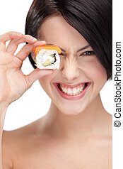 Young girl holding sushi and smiling