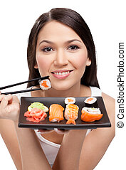 Young attractive woman holding sushi with a chopsticks