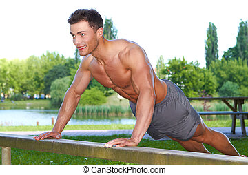 Fitness man in park making push ups