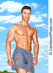 Muscular man posing in park at summer - Muscular man posing...
