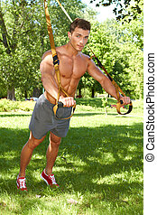 Full body of fitness man in park at summer time
