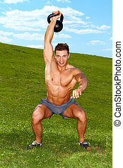 Exercises with kettlebell in sunny weather