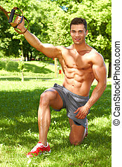 Stretch exercises in park - Muscular male doing stretch...