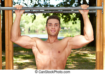 Good looking male doing exercises in park