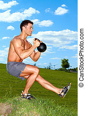 Exercises with kettlebell in sunny weather - Man Exercises...