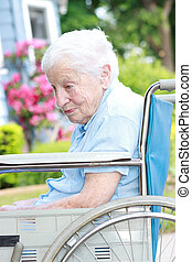 Senior lady in wheel chair in front of house with pink...