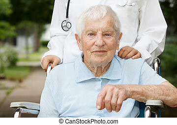 Happy senior lady in wheelchair with her caregiver