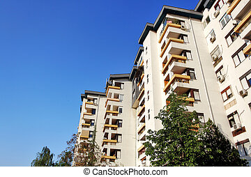 apartment complex with trees infront and blue sky