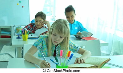 Pupils at school - Three cute school children busy doing...
