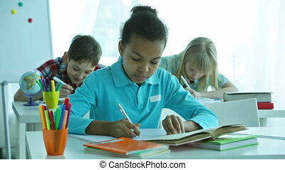 Lesson - Pensive pupils doing tasks during the lesson,...