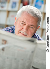 Elderly man with mustache reading paper in library - Senior...
