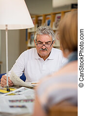 Senior man reading newspaper with wife in library - Retired...
