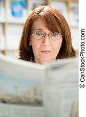 Elderly woman with glasses reading newspaper in library -...