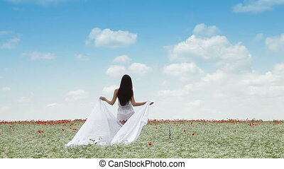 Young Woman With White Scarf Walking In a Field