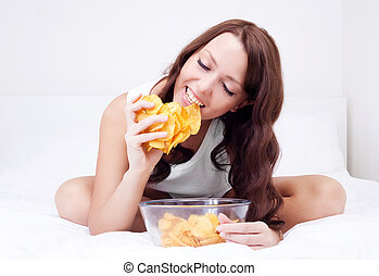 woman with chips - pretty woman eating potato chips in bed...