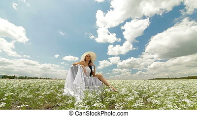 Young Woman On White Field - A young woman in a white hat...