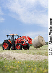 Tractor Hauling Round Bale - Tractor hauling a round bale an...