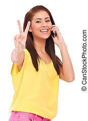 casual woman with phone and victory gesture