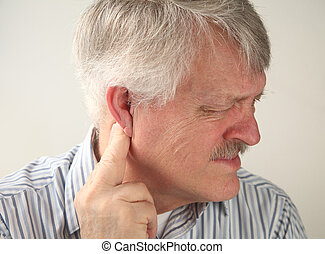 pain around the ear - a senior man suffers from pressure...
