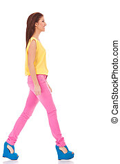 casual woman walking - side view of a young casual woman...