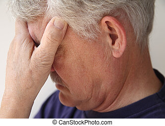 older man depressed or grieving - a senior with his hand...