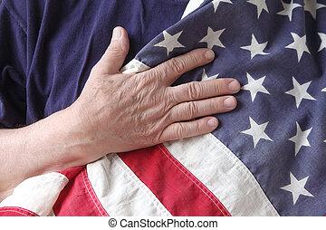 U.S. flag held to the chest - a man's hand on a USA flag...