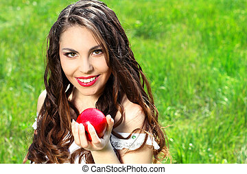 Beautiful young woman with red lips and long hair present red apple on the nature background