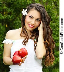 Natural  young woman with happy smile, present red apples