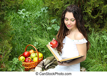 Beautiful girl reading the book with apples on Fairy tale