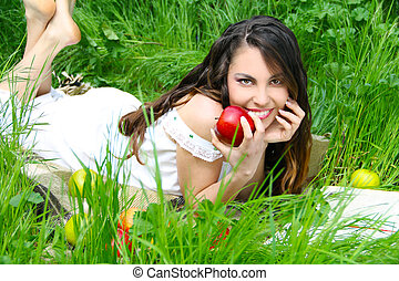 Happy smiling young women with red apple on the green field, outdoors