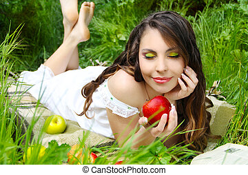 Satisfied young women with red apple on the green field, outdoors