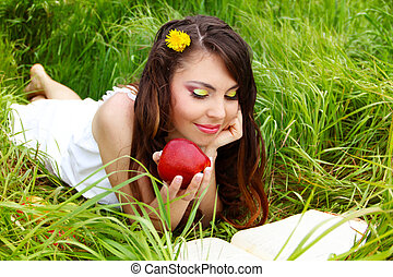 young women with red apple read the book on the green field, outdoors