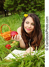 Portrait a pretty young women with red apple on the green field, outdoors