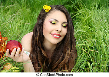 Portrait a pretty young women with red apple on the green field