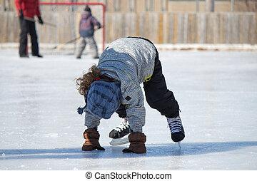 Child at the ice skating rink - Child playing and skating at...