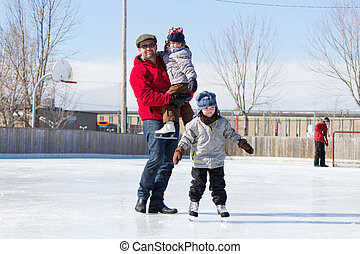 Happy family at the skating rink - Father with son and...