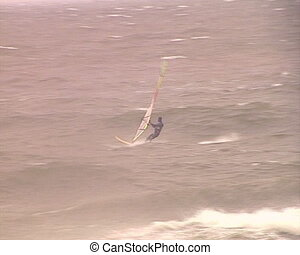 Brave windsurfers sailing between nasty stormy heavy sea...