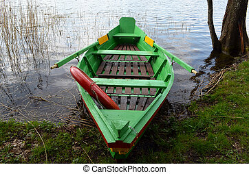 Rowing wooden boat on lake shore and resque circle - Rowing...