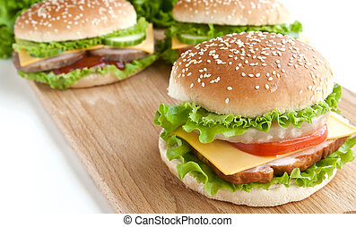 three burger with meat and vegetables on wood plate