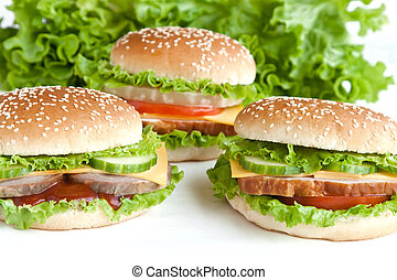 three burger with meat and vegetables