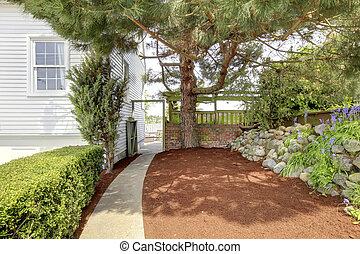 Side yard with walk way and large tree near white house. -...