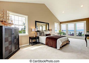 Classic luxury large bedroom with water view and carpet. -...