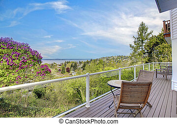 Large deck with furniture and water view over green.