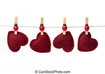Hanging hearts - Four red hearts hanging on a clothesline,...