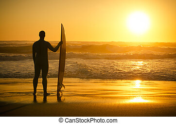 A surfer watching the waves at sunset in Portugal