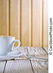 white coffee cup and spoon on old table