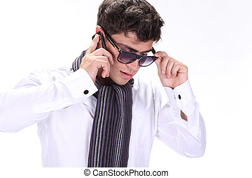 Fashion Man in sunglasses talking on mobile phone isolated on white