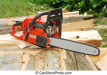 chainsaw over a heap of logs