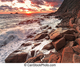 Porth Nanven - Waves crash against the rocks at sunset at...