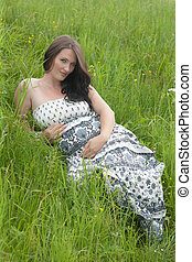 the pregnant woman in a grass